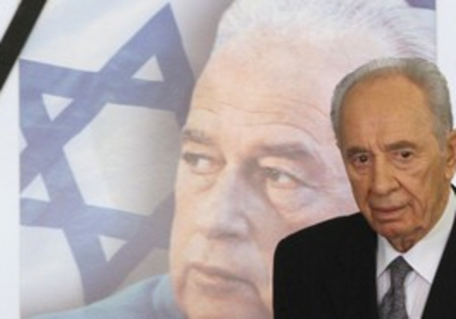PRESIDENT SHIMON Peres walks past a picture of Yit