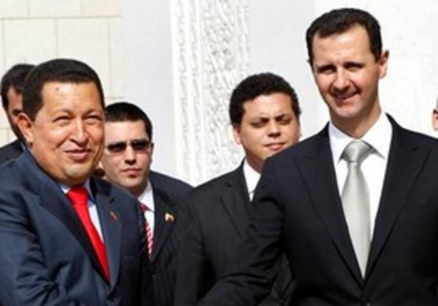 Hugo Chavez, left, shakes hands Syrian President