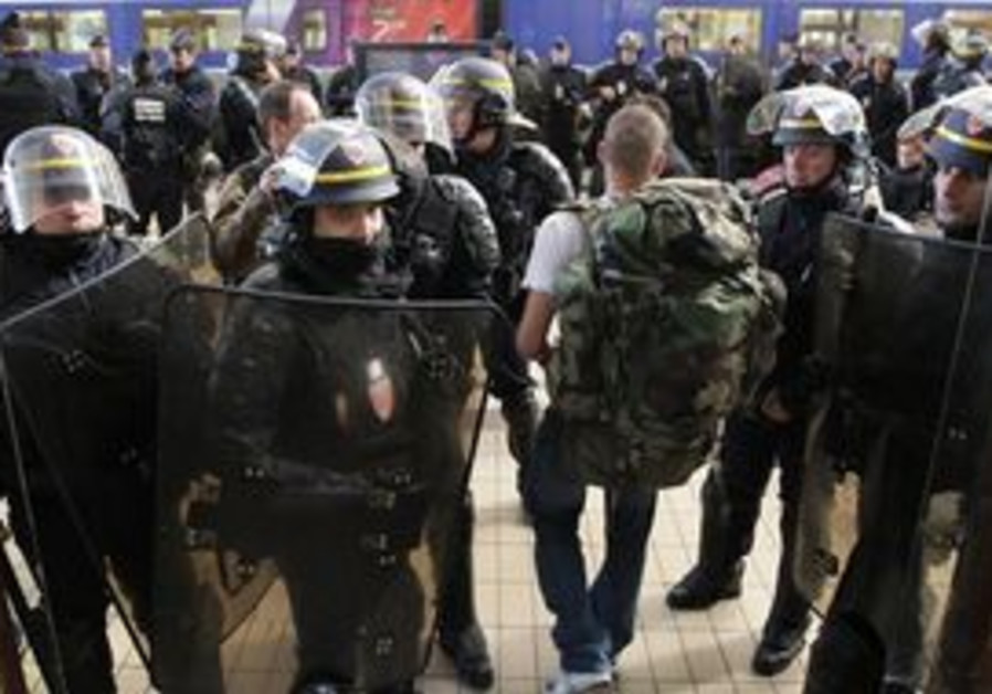 French riot police officers secure the area at the