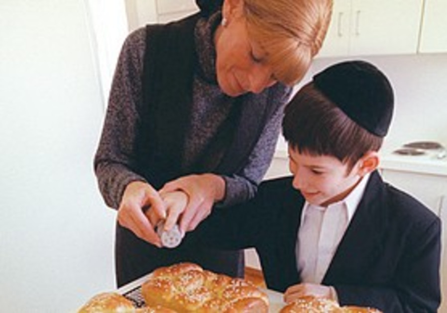 A MOTHER helps her son prepare hallot for Shabbat.