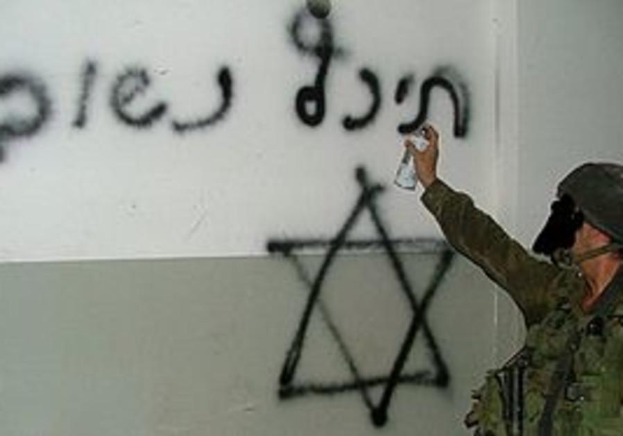 IDF soldier spraying grafitti
