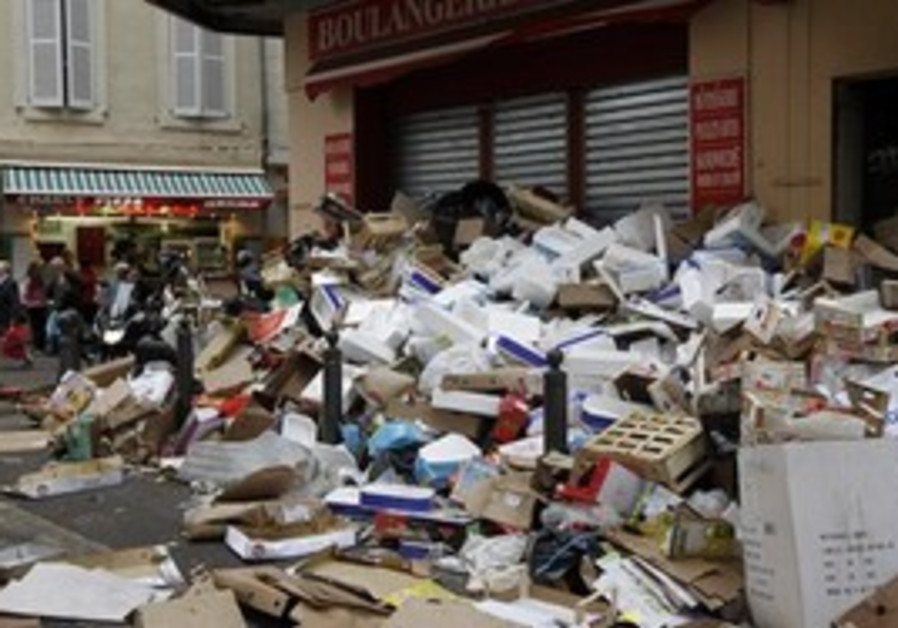 People walk near piles of garbage in Marseille, so