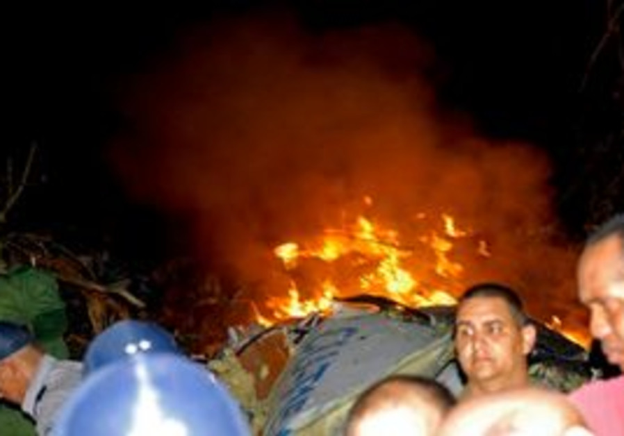 Flames emerge from the wreckage of a Cuban airline