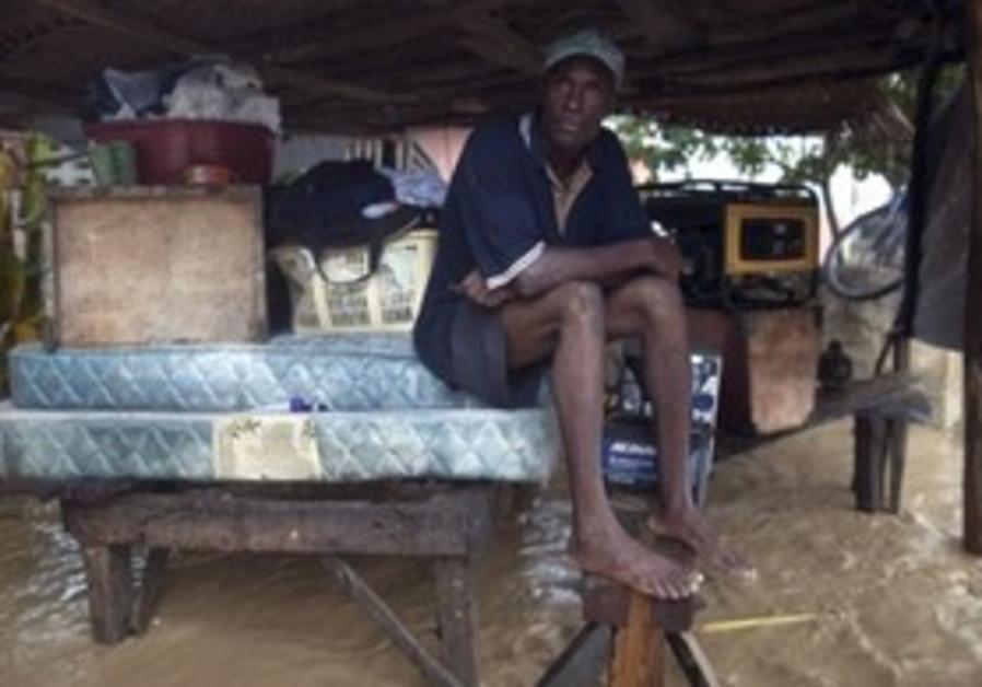 A man waits in his flooded home in Haiti, Nov. 5.