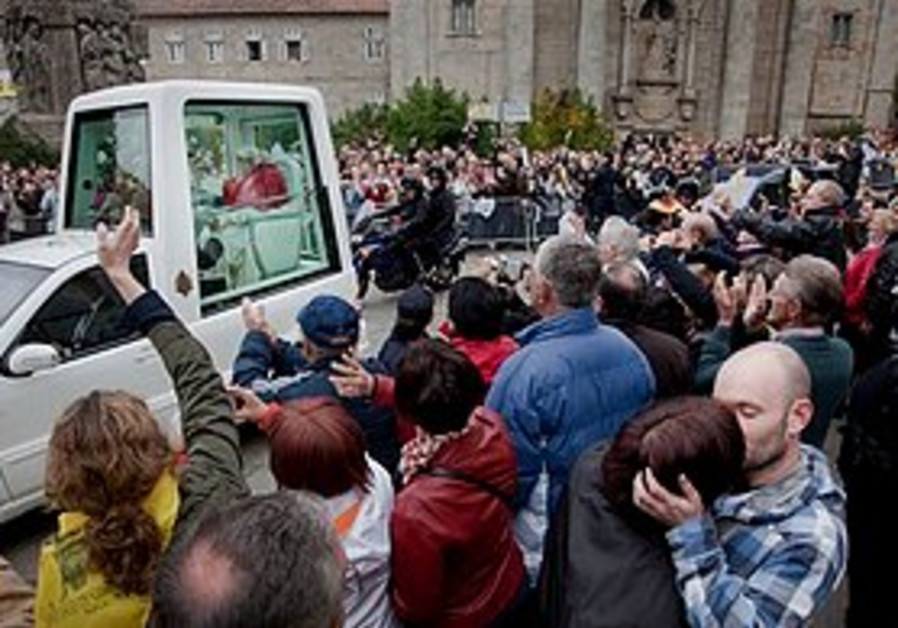 A gay couple kisses in protest of pope's visit.