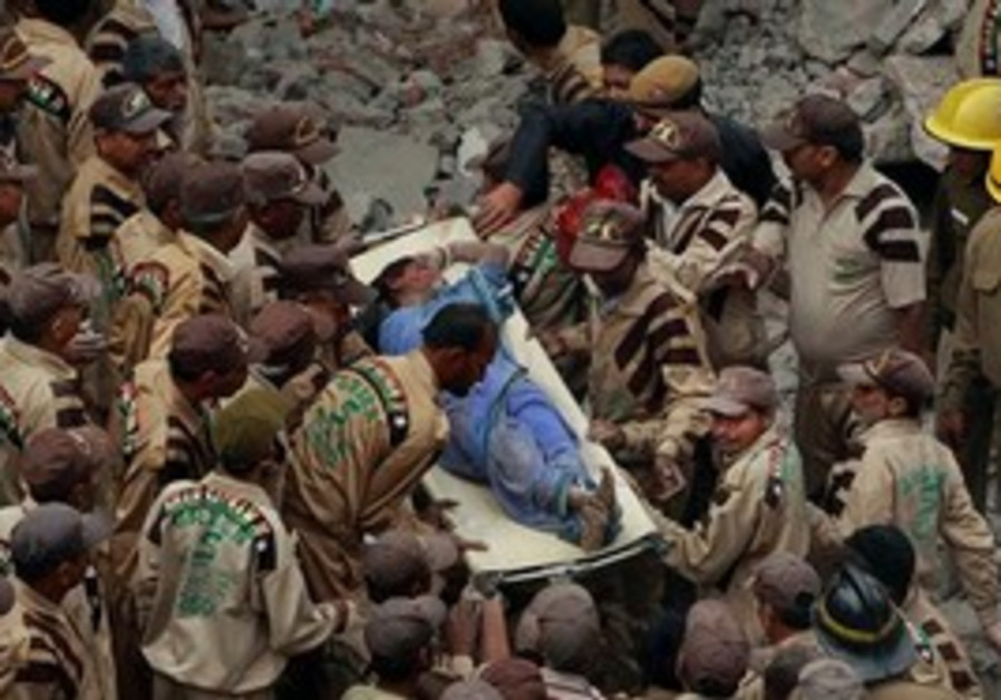 Indian rescue workers pull the body of a woman fro