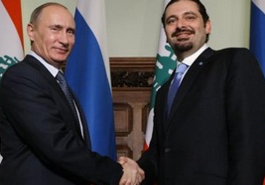 Vladimir Putin and Sa'ad Harir shake hands