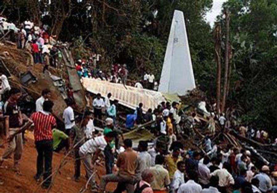 Civilians crowd around Air India flight remains.