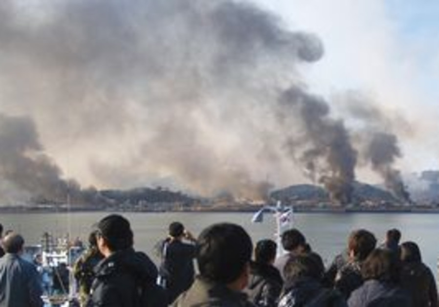 SOUTH KOREAN villagers watch smoke rising from Yeo