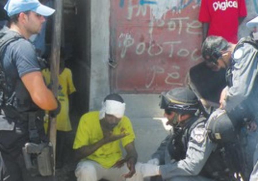 ISRAELI POLICEMEN administer first-aid in Haiti