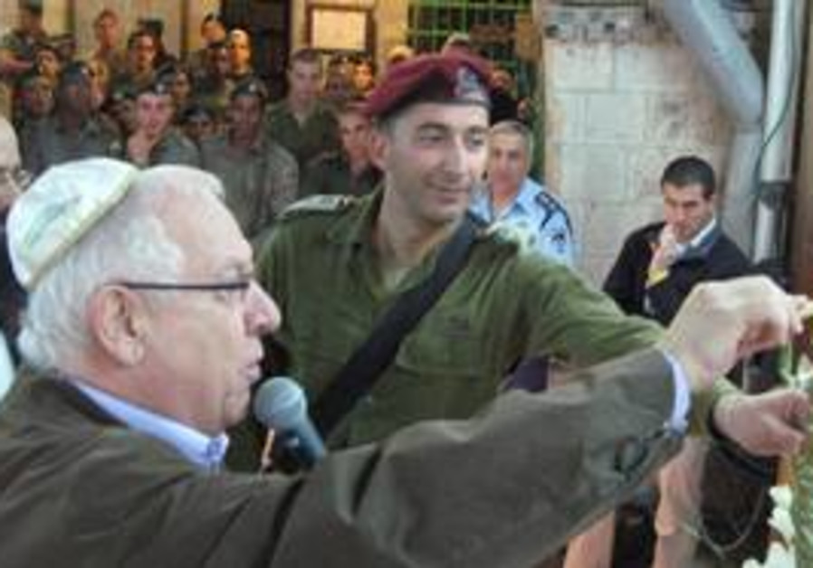 Knesset Speaker Reuven Rivlin lighting candles.