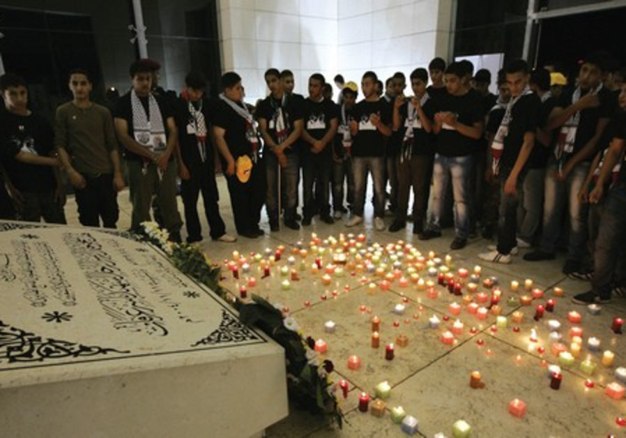 Youths light candles at the Arafat's tomb