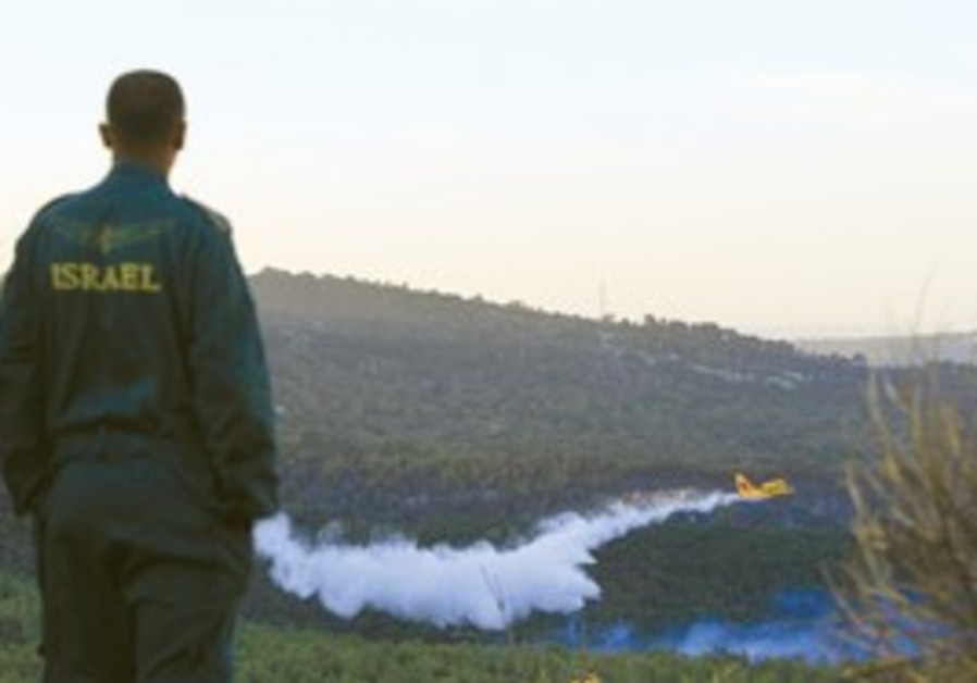 AN IDF soldier watches the firefighting operation