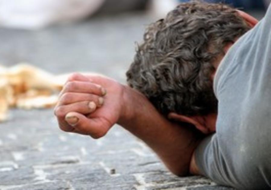 A homeless man lies on a sidewalk