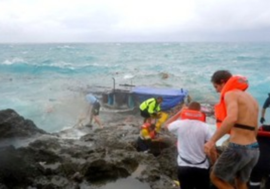 Rescuers on the rocky shores of Christmas Island