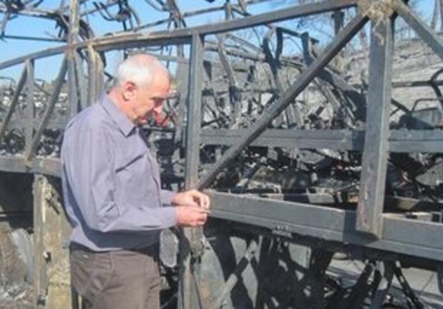 Vilna'i examining burnt out bus in Carmel fire