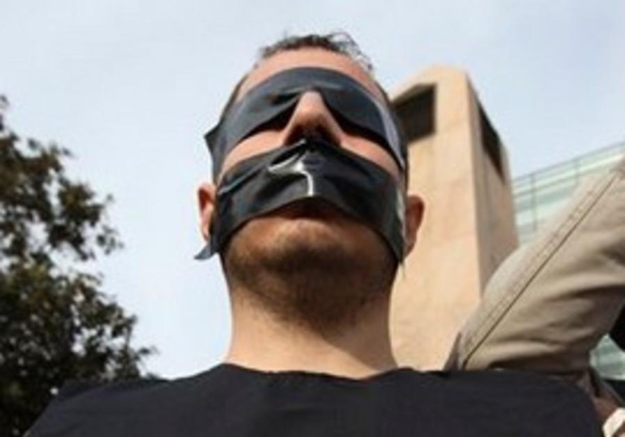 Syrian Kurdish activist tapes his eyes, mouth.