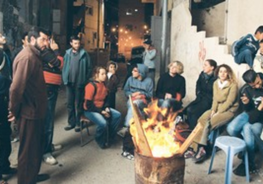 Activists and Silwan residents warm up by a fire.