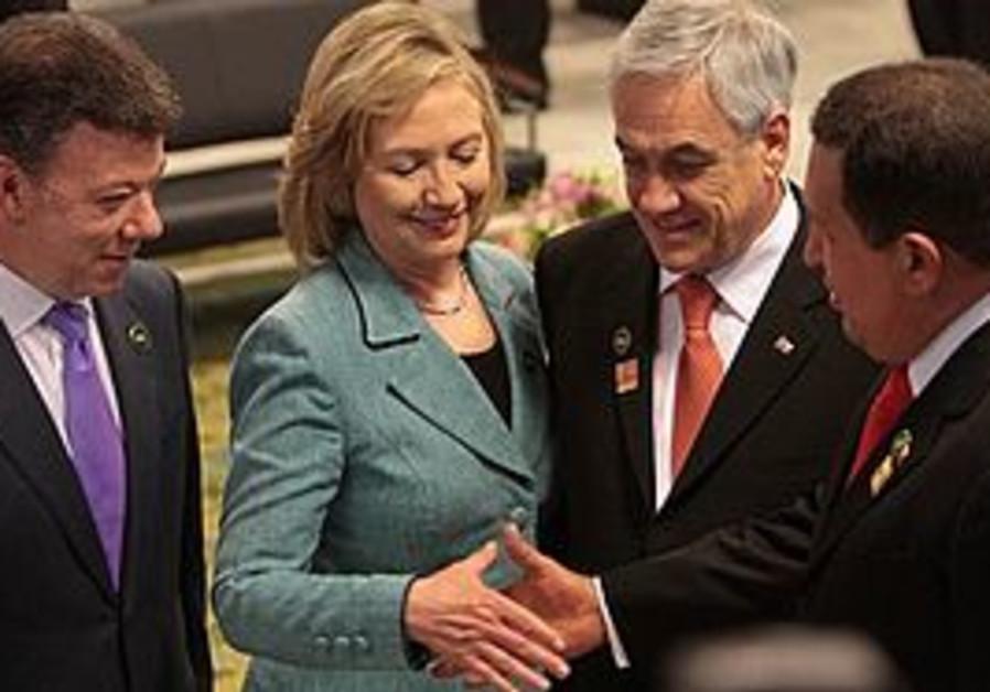 Hilary Clinton shakes hands with Hugo Chavez