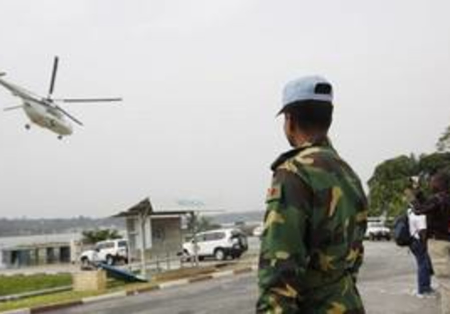 A UN soldier looks on as a helicopter takes off