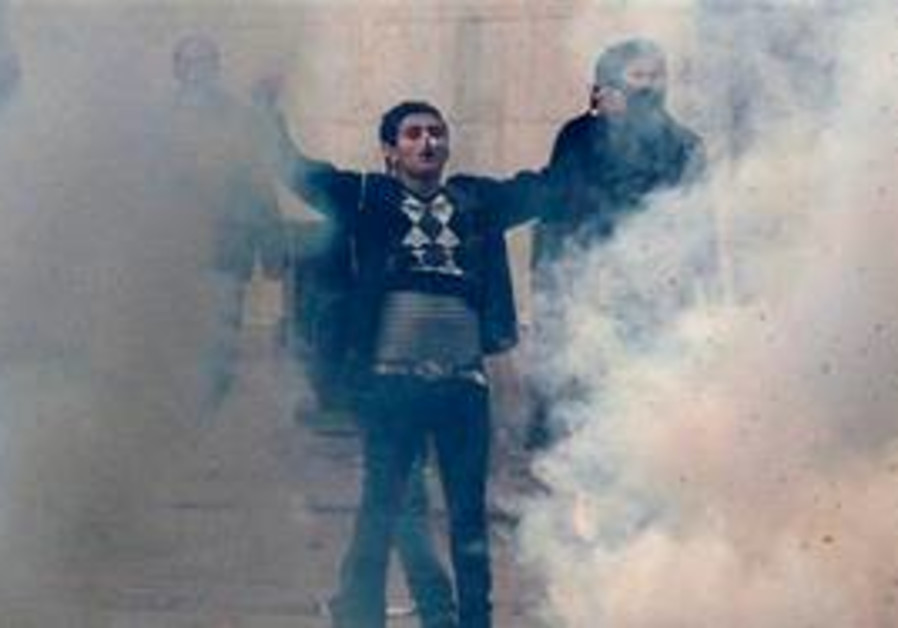 Tunisian rioter stands in tear gas clouds