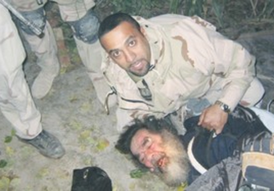 AN IRAQI-AMERICAN soldier pins deposed Iraqi leade