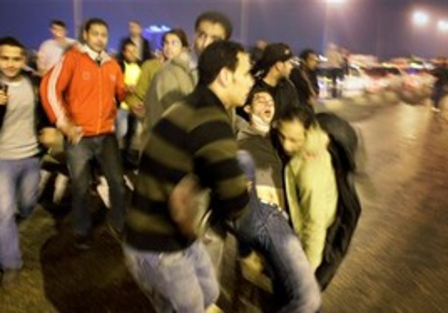 Injured man is carried away at clashes in Cairo.