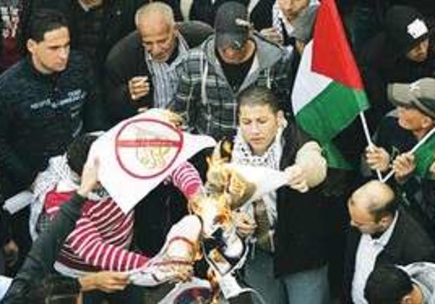 Fatah supporters burn Al-Jazeera logos in Ramallah