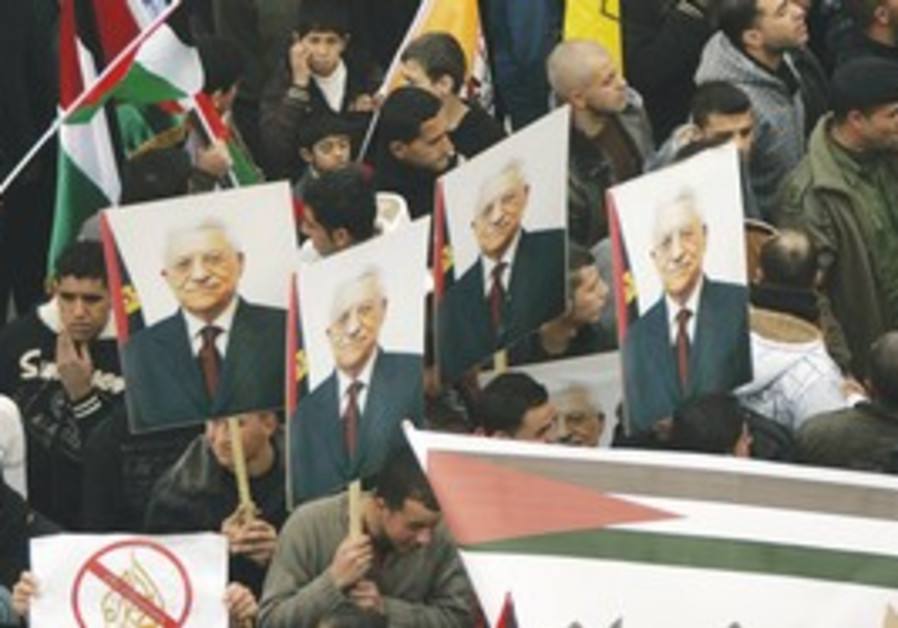 Fatah supporters hold portraits of Mahmoud Abbas.