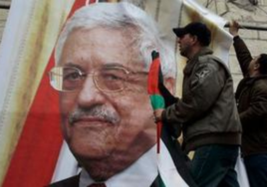 Fatah supporters hang Abbas poster