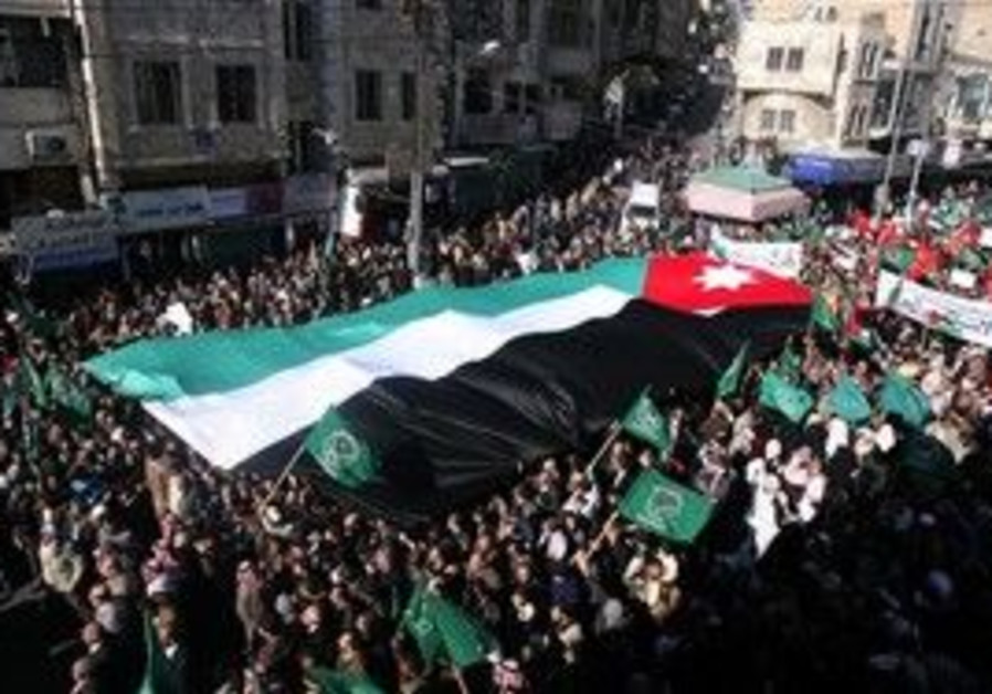 ordanian protesters hold a giant national flag.
