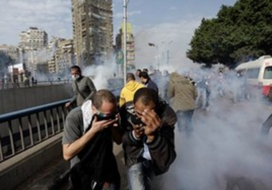 Egyptian protesters run for a cover from tear gas.