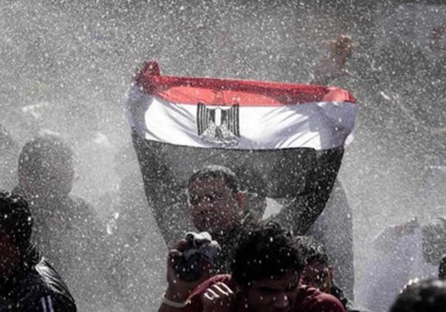 Egyptian protester with flag, water cannon