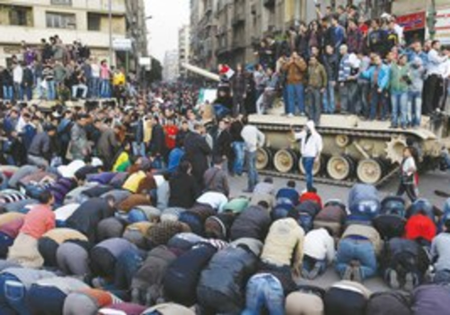 Protestors pray in front of a tank in Cairo.