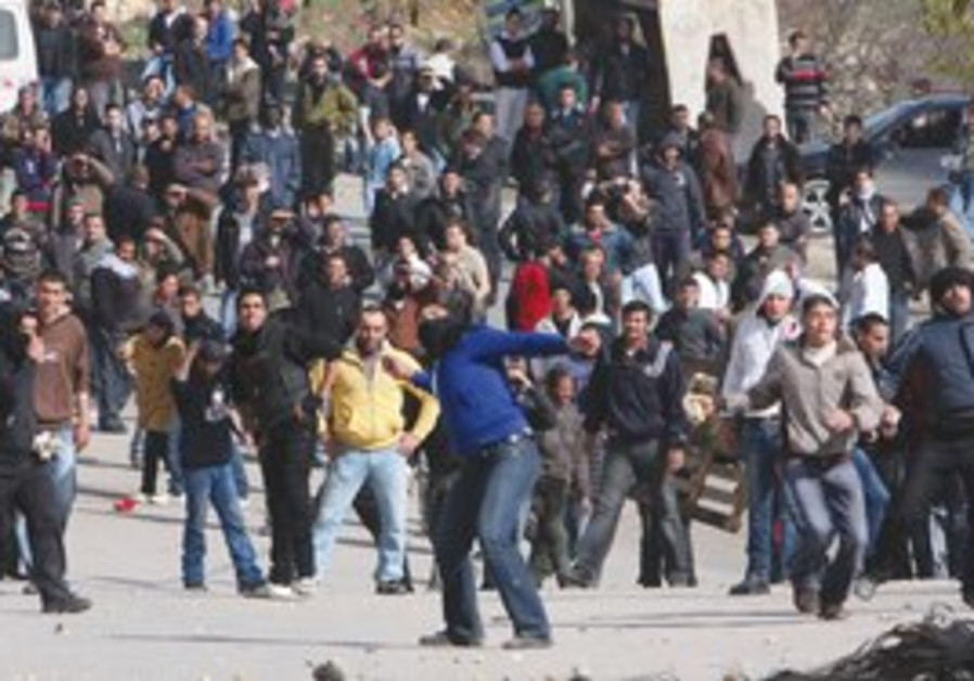 Palestinians throw stones after Ikhlayl funeral.
