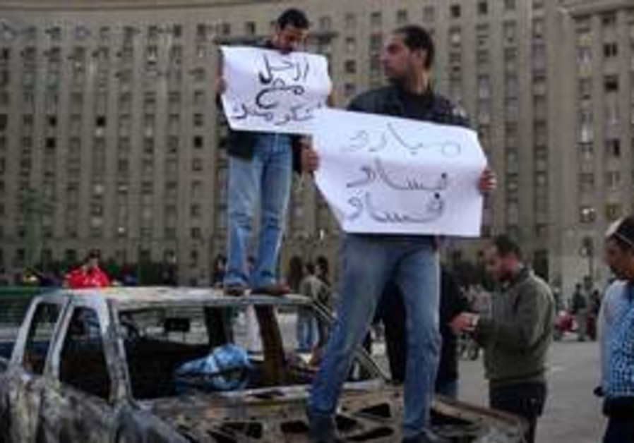 Egyptian protesters hold signs atop a burnt car