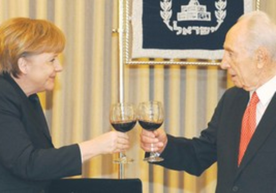 Peres and Merkel clink glasses, Tuesday.