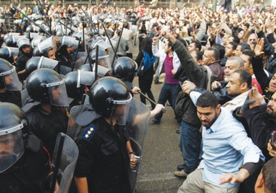Egyptian anti-riot police clash with protesters.