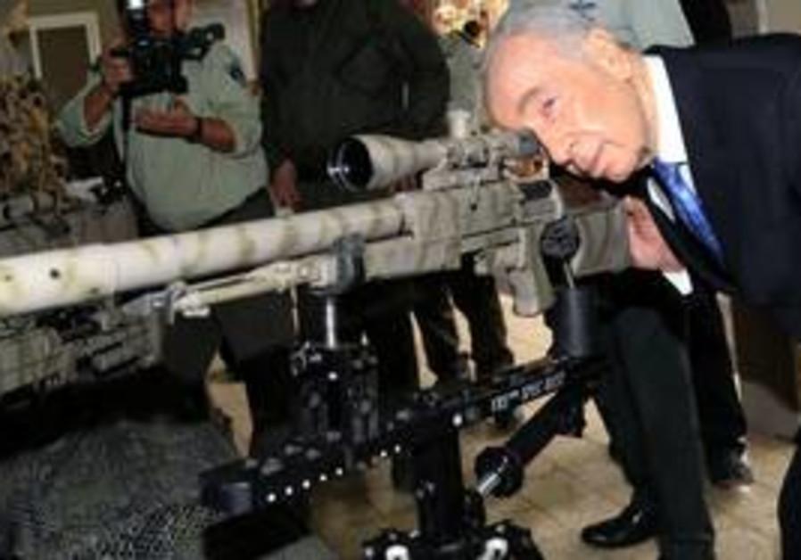 President Shimon Peres inspecting gun