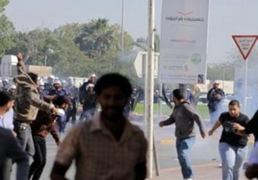 Riot police chase Bahraini demonstrators.