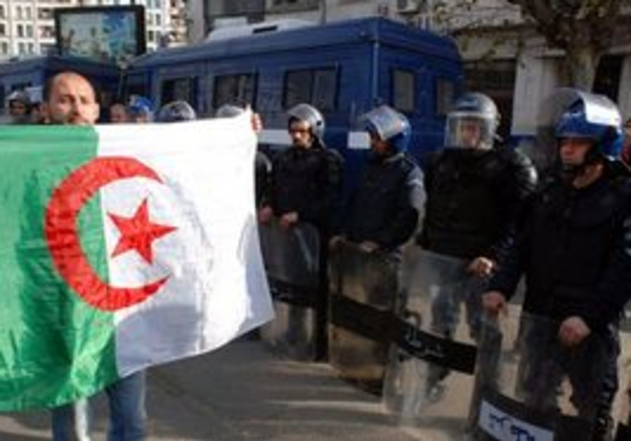 A man holds an Algerian flag in front of police.