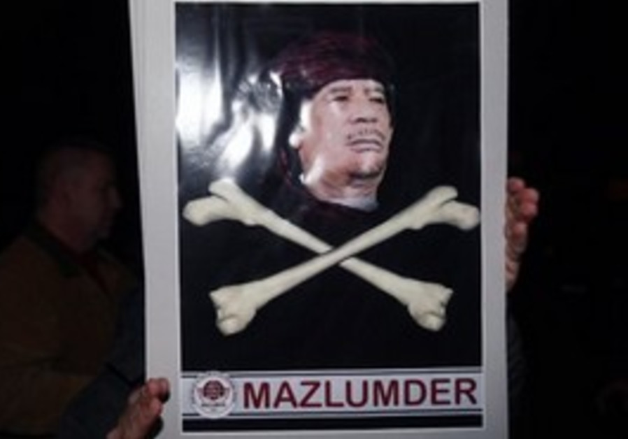 Pro-Islamic Turk holds a poster of Libyan leader