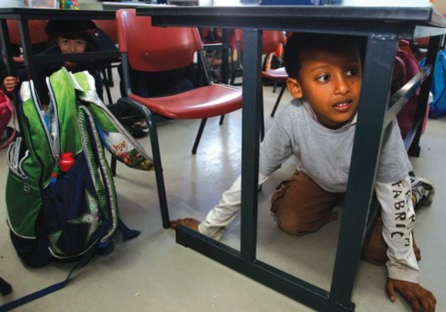 Children hiding under tabels, earthquake (file)