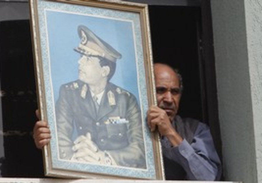 Man holds a picture of Gaddafi from a bank window.