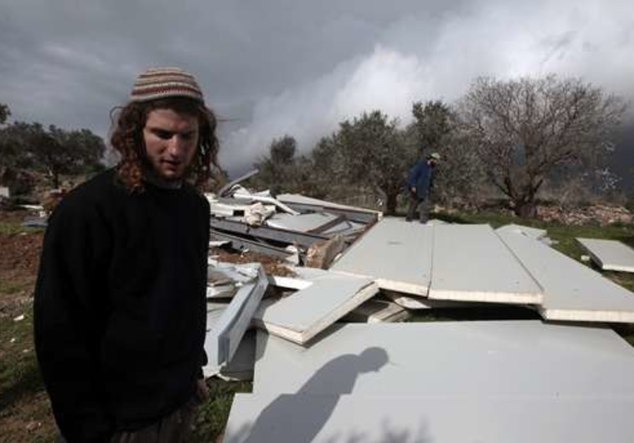 A boy stands by razed structures in Havat Gilad