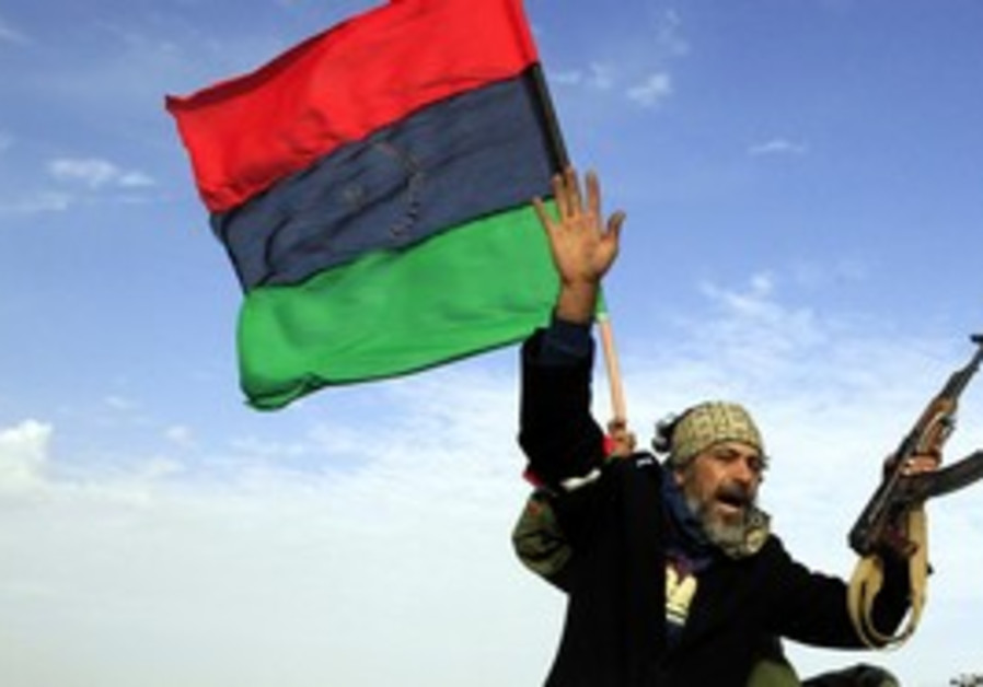 Libyan gestures atop a car