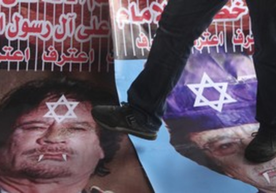 Protesters step on poster of Gaddafi, Jewish star