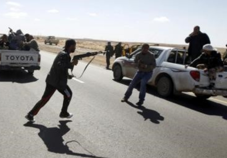 A rebel fighter runs with a rifle in Libya