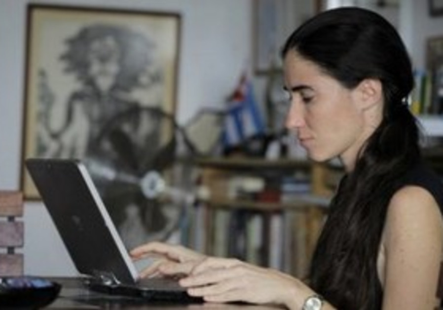 Yoani Sanchez works on her laptop at her home