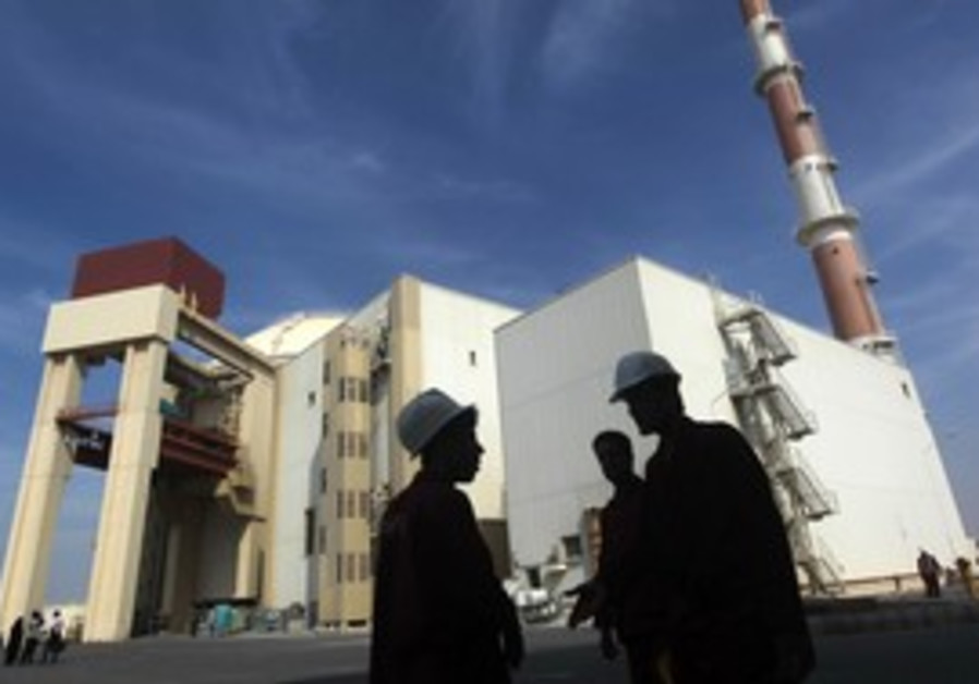 Iranian workers stand in front of Bushehr.